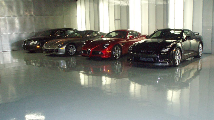 A line of cars parked in a garage with flooring made with Ohio Garage Interiors'