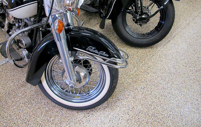 An example of Ohio Garage Interiors' garage flooring epoxy coatings along with the front end of two motorcycles.