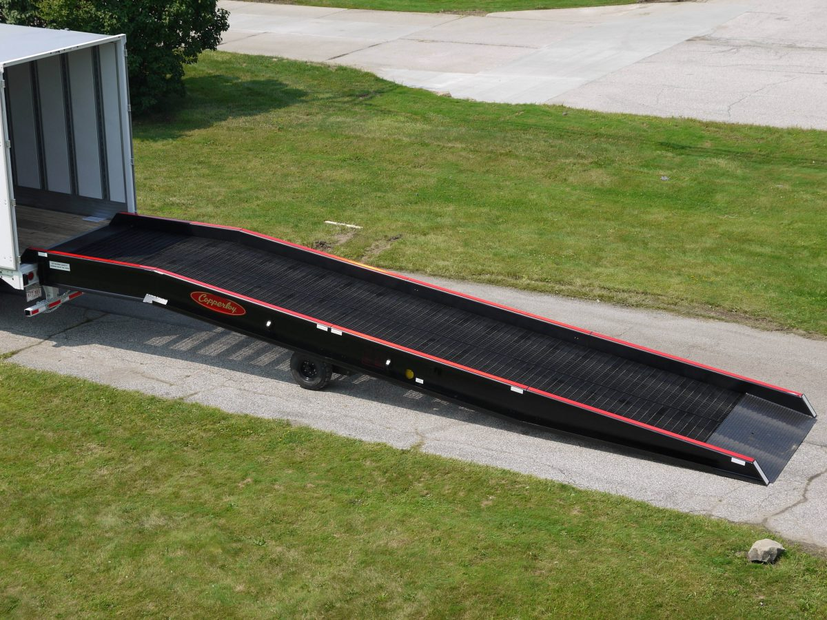 A Copperloy portable dock ramp connected to the back of a truck.