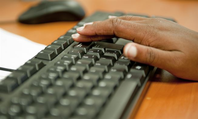 A hand typing on a keyboard, representing IT companies like QualityIP.